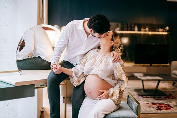 Couple s'embrassant pour une séance photo grossesse